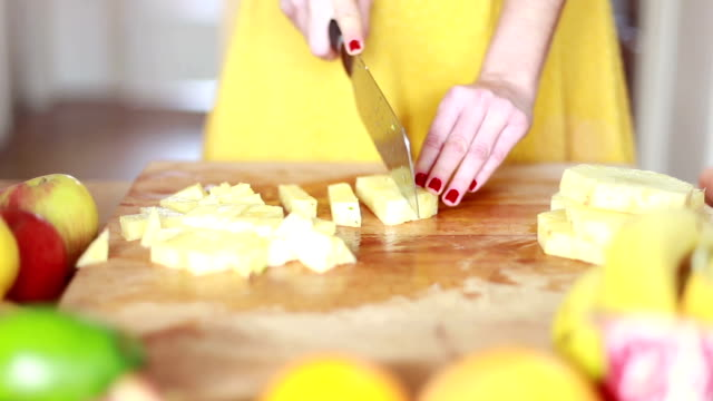View of woman hands cutting pineapple on small pieces video