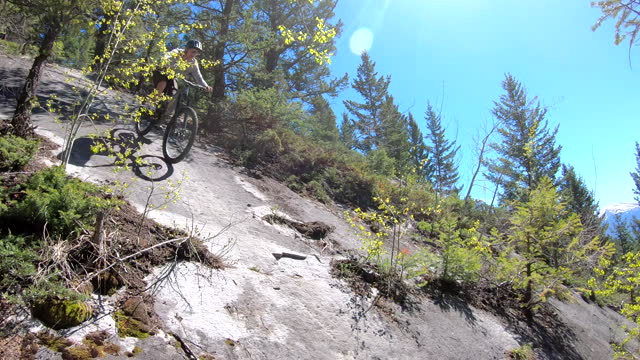 stockvideo's en b-roll-footage met view of young man mountain biking in forest - minder dan 10 seconden
