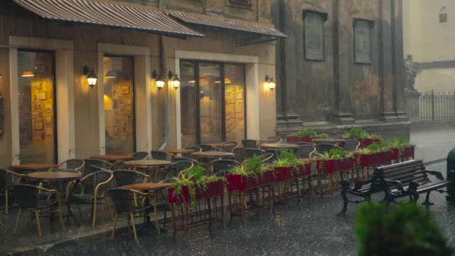 view on a wet summer terrace of the cafe with flowers, tables and chairs in the street in rainy weather. - terrazza video stock e b–roll