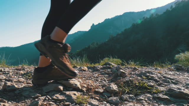 View on Feet of Traveler Woman Hiking Walking on the Top of Cliff in Mountain. Slow Motion View on Feet of Traveler Woman Hiking Walking on the Top of Cliff in Mountain. Slow Motion in 96 fps. Walking on Rocks. Camera follow hiker's feet on top of the mountain. Achieving the goal. Forward movement, motivation. Sunny day. footpath stock videos & royalty-free footage