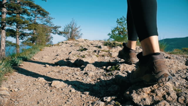 View on Feet of Traveler Woman Hiking Walking on the Top of Cliff in Mountain. Slow Motion video