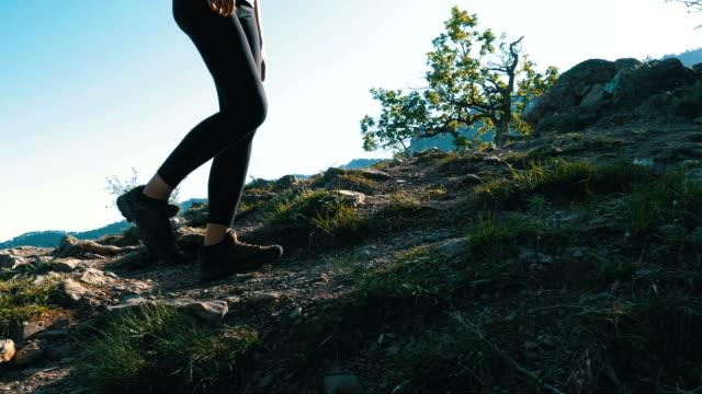 山の崖上を歩いてハイキング旅行者女性のフィートで表示。岩の上を歩く - 後に続く点の映像素材/bロール