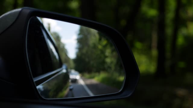 View out the rearview mirror as car drives on country road. 4K View out the rearview mirror as car drives on country road rear view mirror stock videos & royalty-free footage