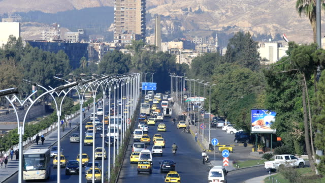 View over circulation in Damascus. A lot of cars on the road in Syria. View over the circulation in Damas, a lot of cars and trucks on the road. A living city even after the war. Buildings and trees in the background. War years in Syria. damascus stock videos & royalty-free footage