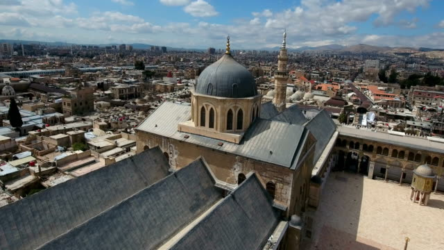 vídeos de stock e filmes b-roll de view over the umayyad mosque in syria. drone is flying around the building exterior of a tower mosque and with the city of damascus in the background. - síria