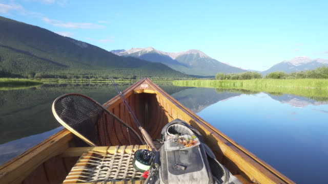 View past bow of wooden canoe with fishing gear, mountain lake  fishing rod stock videos & royalty-free footage