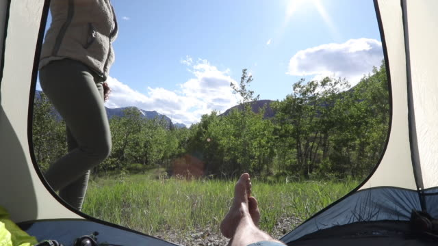 View past tenters legs to mountain meadow and sunlight
