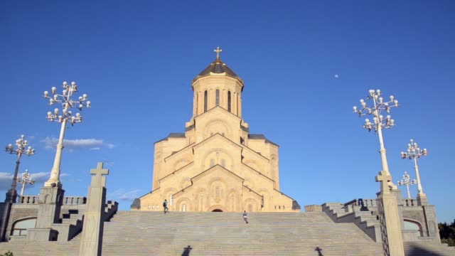 View Sameba bottom girl climbs the stairs to the entrance of Holy Trinity Cathedral of Tbilisi