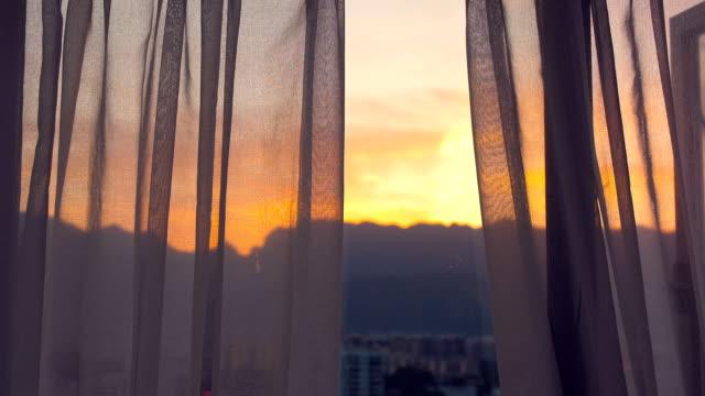 vídeos de stock e filmes b-roll de view the sunset through curtains - living room background