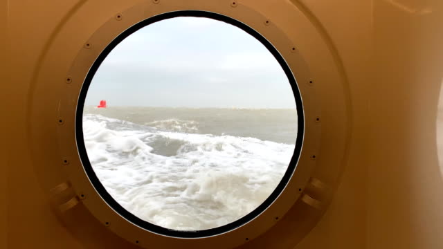 View through a porthole on a stormy sea with waves hitting the ship