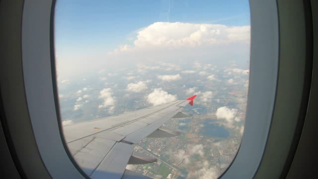 view through an airplane window on the sky and clouds. - okno filmów i materiałów b-roll