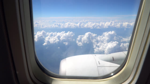 View through an airplane window on the sky and clouds