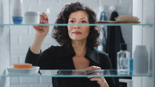 View Through Bathroom Cabinet Of Mature Woman Getting Ready And Putting In Earrings View through bathroom cabinet of mature woman opening doors  before getting ready and putting in earrings - shot in slow motion cabinet stock videos & royalty-free footage