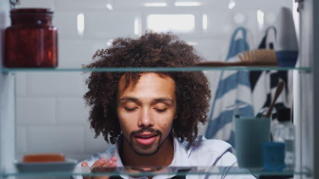 посмотреть через ванную комнату кабинет молодого человека готовится к работе и увлажняющий кожу - уход за кожей стоковые видео и кадры b-roll