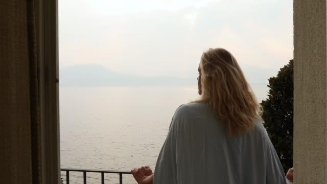 vídeos de stock e filmes b-roll de view through doorway, of woman on veranda at sunrise - lago maggiore