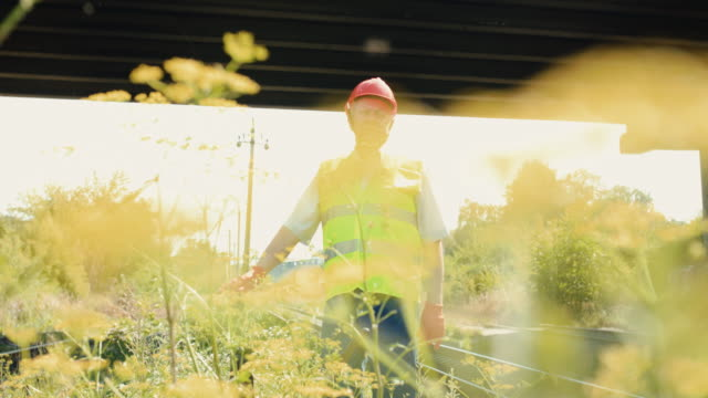 View through grass of senior engineer leans hand and looks at camera on railway video