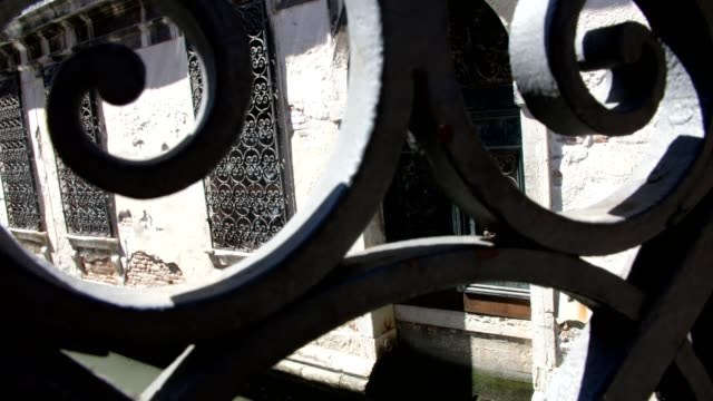 view through the openwork, forged bridge to the old building, standing on the water of the canal, with forged old bars on the windows VENICE, ITALY - JULY 7, 2018: view through the openwork, forged bridge to the old building, standing on the water of the canal, with forged old bars on the windows. neo gothic architecture stock videos & royalty-free footage