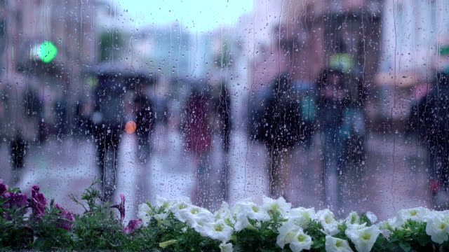 View through the window on rainy day. Raindrops on window glass, people walk on city street in rainy day, blurred silhouettes of people. Concept of shopping, walking, lifestyle, weather, seasons, modern city