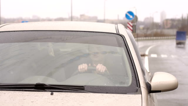 View through the windshield of the car on the girl behind the wheel of car.