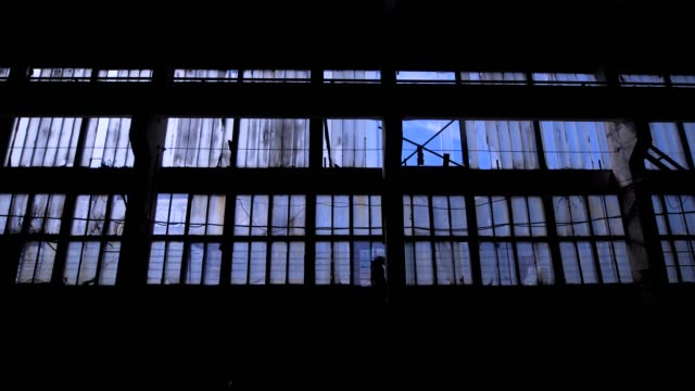 View to blue sky through the windows of old grungy industrial building video