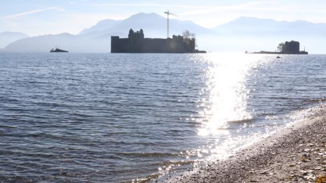 vídeos de stock e filmes b-roll de view to castle, lake and distant mountains - lago maggiore