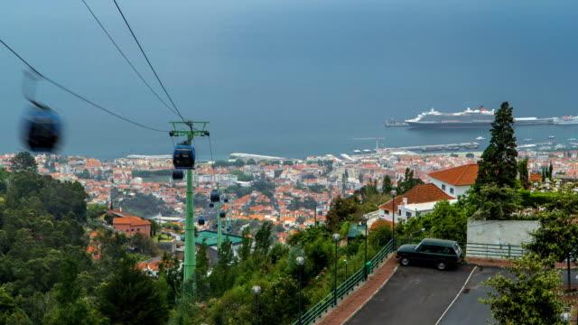 vídeos de stock e filmes b-roll de vista para o oceano com barco sobre os telhados com cabo de madeira timelapse de aluguer - funchal madeira