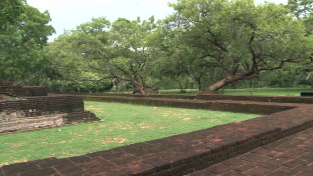 View to the ruins of the ancient city and trees in Polonnaruwa, Sri Lanka. View to the ruins of the ancient city and trees in Polonnaruwa, Sri Lanka. Polonnaruwa is a UNESCO World Heritage site. sri lankan culture stock videos & royalty-free footage