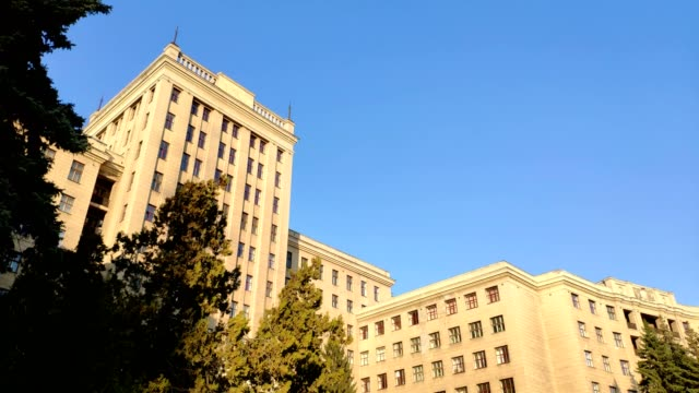 view up of state industry building or gosprom built in construction art over blue sky, sun ray in the sky - balaustrata video stock e b–roll
