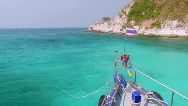 Viewi of cliffy shore of island Rin, Thailand. View from sailing boat with hibiscus on stempost video