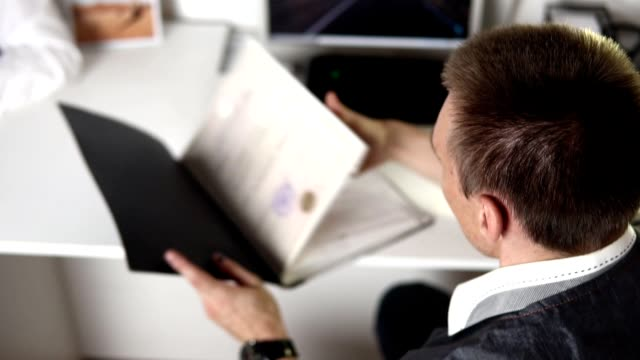 vidéos et rushes de affichage des documents dans un dossier noir sur la table - dossier document