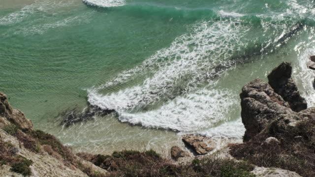 views down onto an idyllic cove near Porthcurno, Cornwall on a sunny autumn day. video