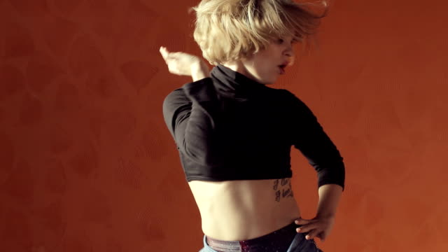 Vigorous blond woman in a short top and tights dancing on orange background video