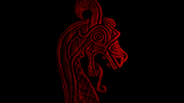 Viking Dragon Carving Lit Up On Black Close-up of Norse dragon head stone carving in fire glow fantasy stock videos & royalty-free footage