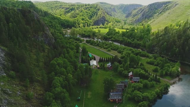 village at the foot of the mountain. aerial view. nature and tranquility - quadcopter filmów i materiałów b-roll