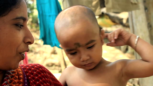 Village baby makes funny faces. video