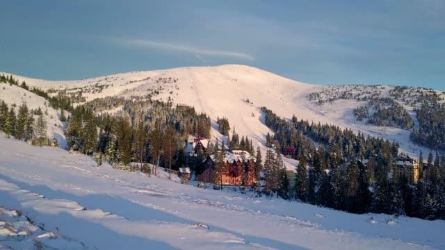 dorf in den bergen im winter am morgen - schneeflocke sonnenaufgang stock-videos und b-roll-filmmaterial