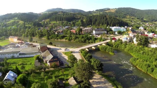 village  with bridge in  small mountain valley. aerial shot - stenhus bildbanksvideor och videomaterial från bakom kulisserna