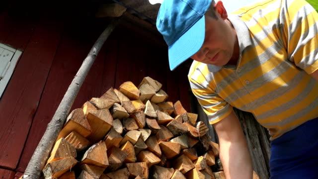 dorfbearbeiter man stapelt brennholz in der nähe von ländlichem holzhaus. 4k - brennholz stock-videos und b-roll-filmmaterial