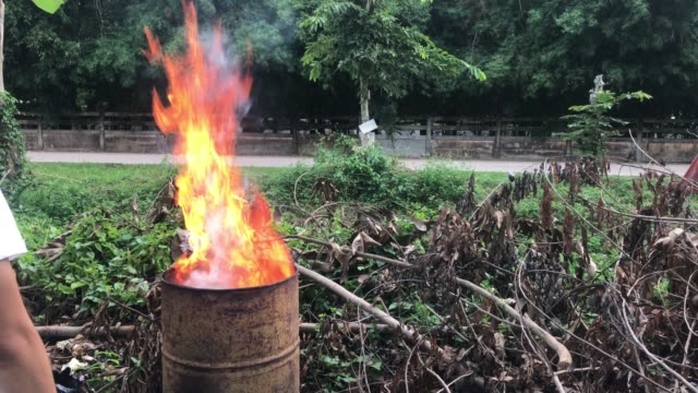 vídeos de stock e filmes b-roll de villagers burn garbage with metal buckets. pollution and air pollution concept. - barrica