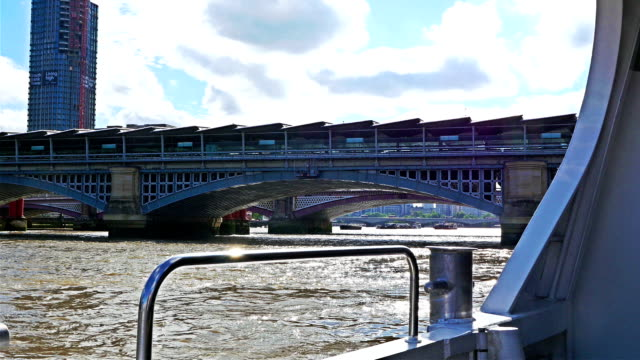 Vind blowing the suit of a businessman on a boat on river Thames, London city center and Shard on the back video