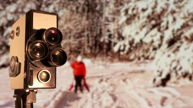 fotocamera vintage da 8 mm di fronte a uno sfarfallio vecchio sfondo cinematografico - christmas movie video stock e b–roll