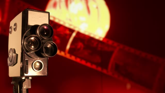 Vintage 8mm film camera in front of flickering old movie background