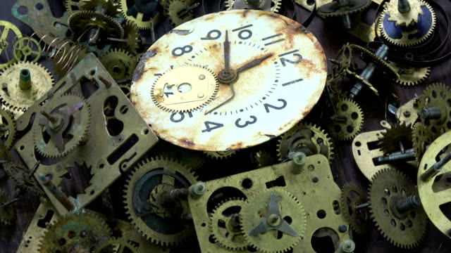 Vintage analog clock brass gears and cogs with rusty dial clock face rotating background video