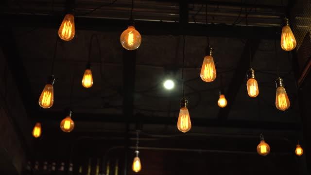 vintage ve retro sarı gece cafe koyu arka plan üzerinde asılı ampul. - avize aydınlatma ürünleri stok videoları ve detay görüntü çekimi
