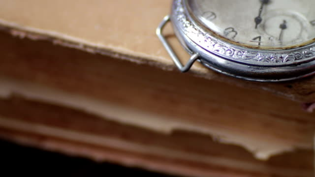 Vintage Antique pocket watch on the background of old books Vintage Antique pocket watch on the background of old books.Vintage pocket watch next to the old faded book, hot pockets stock videos & royalty-free footage