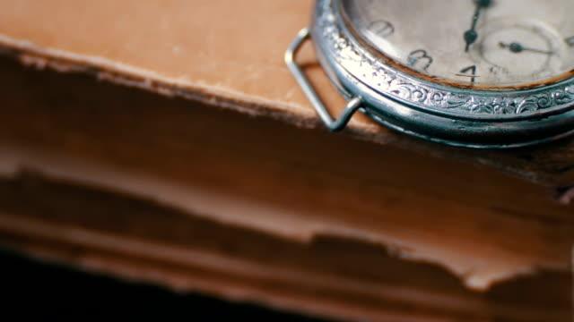 vídeos y material grabado en eventos de stock de reloj de bolsillo antiguo vintage en el fondo de libros antiguos. - estilo de vida rural
