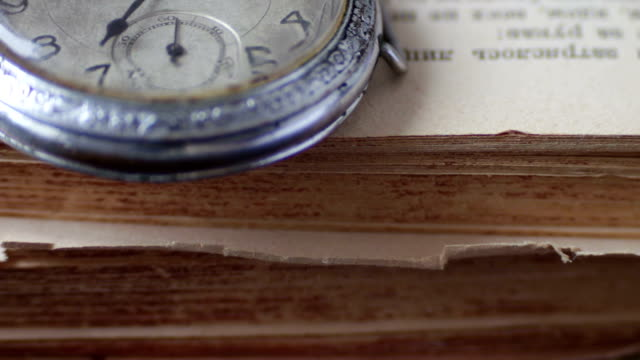 Vintage Antique pocket watch on the background of old books Vintage pocket watch next to the old faded book,Vintage Antique pocket watch on the background of old books hot pockets stock videos & royalty-free footage