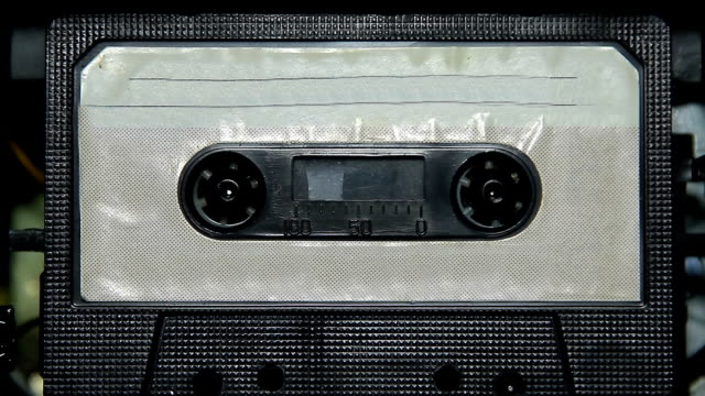 vintage audio cassette tape with a blank white label - musicassetta video stock e b–roll