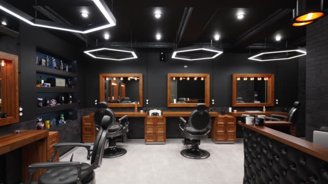 Vintage barbershop interior - movement along the chairs, wooden tables and mirrors. Stylish hair studio indoors. Stylish beauty salon design with modern lighting and lamps
