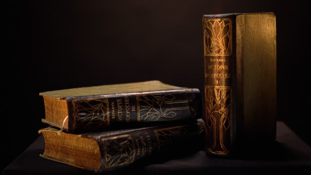 Vintage books with dark leather binding and patterns on isolated background. Stock footage. Old book with simple gilded patterns on cover